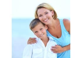 幸福的母子在海滩上拥抱的特写肖像_11182557