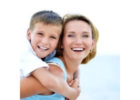 幸福的母子在海滩上拥抱的特写肖像_11182558