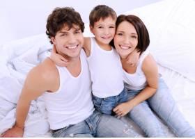 幸福的父母和小孩坐在床上的高角肖像_10729418