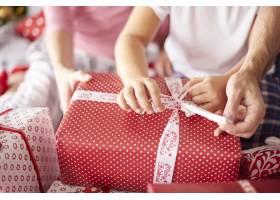 在拆开圣诞礼物时家人的手紧贴在一起_11727975
