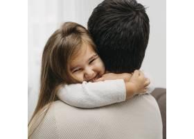 微笑的女儿在家里拥抱她的父亲_11904694