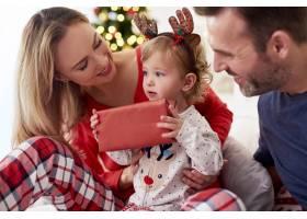 在父母躺在床上打开圣诞礼物_11725333