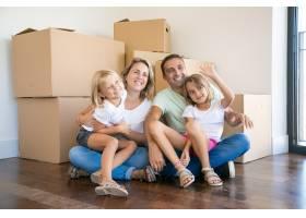 微笑的家庭孩子们坐在纸箱附近的地板上放_11076409