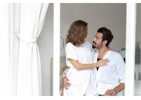 微笑的情侣放松情侣们在床上拥抱_11993795