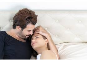 微笑的情侣放松情侣们在床上拥抱_11993812