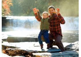 微笑的父亲和他的儿子在阳光下绿树成荫的公_10400158