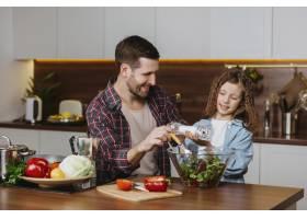 微笑的父亲和女儿在厨房做饭的前景_11765744