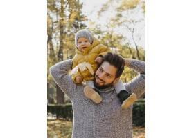 微笑的爸爸带着他的孩子在户外_11904663