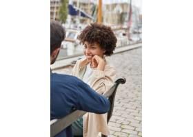 坐在长椅上的开朗迷人的女子照片露出牙齿_12086803
