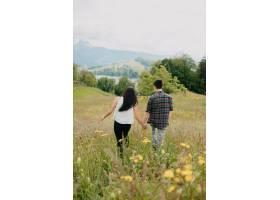 垂直拍摄的一对相爱的年轻夫妇走在田野里_10835170