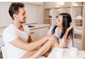 微笑的黑发男子抚摸着女友的膝盖而她在厨_10786213