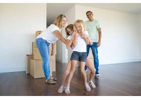 快乐的家庭夫妇和两个孩子在搬进新公寓时玩_11072676