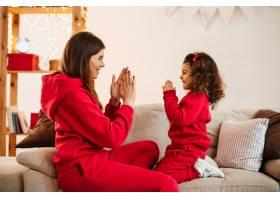 快乐的年轻妈妈和女儿在沙发上玩耍迷人的_12431648