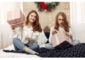 女孩们坐在床上拿着礼品盒的女人朋友们_10703481