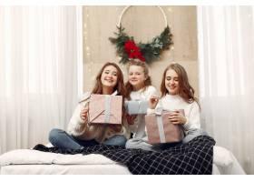 女孩们坐在床上拿着礼品盒的女人朋友们_10703482