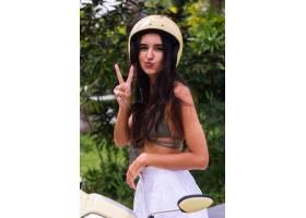 快乐晒黑的女人在户外戴着头盔骑摩托车_11305301