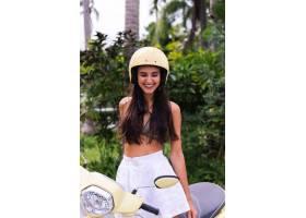 快乐晒黑的女人在户外戴着头盔骑摩托车_11305313