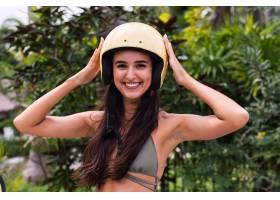 快乐晒黑的女人在户外戴着头盔骑摩托车_11305315