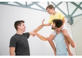 快乐的同性恋夫妇和他们快乐的儿子在家里玩_11298076