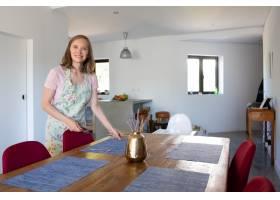 快乐的女人穿着围裙在家里为家庭聚餐提供_9649901