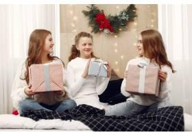 女孩们坐在床上拿着礼品盒的女人朋友们_10703485