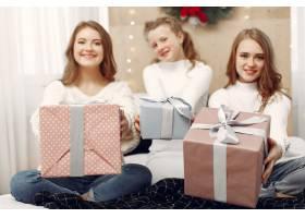 女孩们坐在床上拿着礼品盒的女人朋友们_10703487