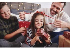 女孩和她的家人打开圣诞礼物_11757115