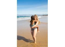 快乐的年轻母亲抱着小女儿抱着孩子在海_11072652