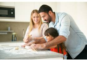 快乐的年轻父母教女儿用凌乱的面粉在厨房桌_9649921