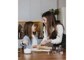 快乐的母女俩在家里的厨房里做饭_11766008