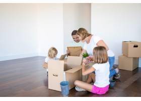 快乐的父母和孩子们在新的空荡荡的公寓里打_10608472