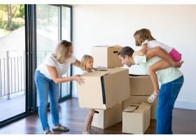 快乐的父母和孩子们庆祝购买公寓打开盒子_10608470
