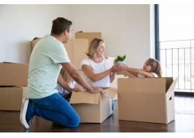 快乐的父母和孩子在新公寓里打开东西坐在_10579292