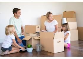 快乐的父母和小女孩在新公寓里打开东西坐_10608473
