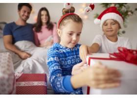 兄弟姐妹在床上打开圣诞礼物_11727968