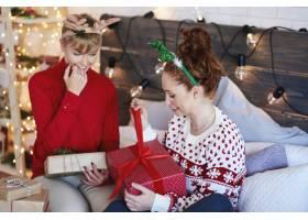 兴奋的女孩在床上打开圣诞礼物_11755844