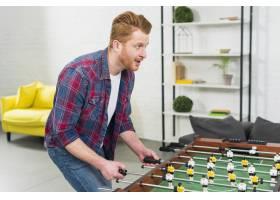 兴奋的年轻人在客厅里玩足球桌上足球比赛_3894143
