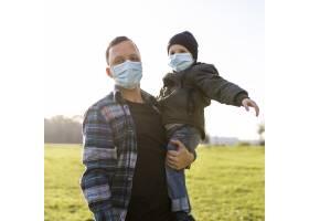 带着医用口罩的父子在公园里_11174469