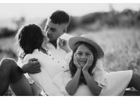带着女儿的年轻家庭在草地上_10298821