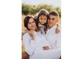 带着女儿的年轻家庭在草地上_10298832