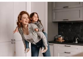 卷曲的妈妈穿着牛仔裤和她的女儿在厨房里玩_12677627
