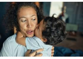 可爱温柔的混血小男孩亲吻他兴奋的年轻妈妈_11554451