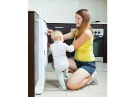 带着蹒跚学步的孩子的妇女使用洗衣机_1469913