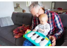 头发花白的爷爷坐在沙发上和婴儿玩耍_9171999