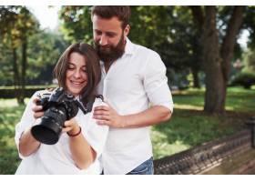 一对微笑的情侣在相机前看照片_10522662