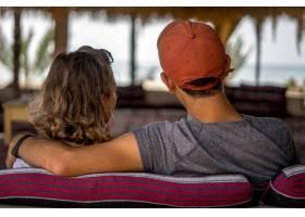 一对相爱的情侣在度假时坐在沙发上看着大海_11061730