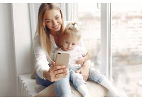 女人用电话穿着白衬衫的母亲正在和她的女_10705766