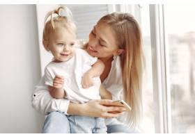 女人用电话穿着白衬衫的母亲正在和她的女_10705770