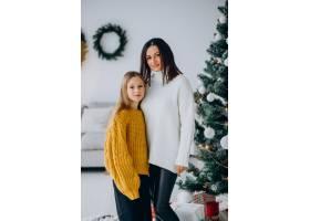 女儿和母亲在圣诞树旁_11980679