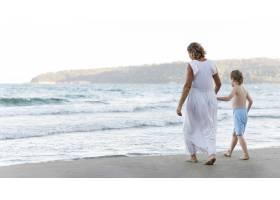 奶奶和孩子在海滩上散步_10849881
